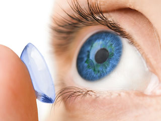 contact lens being placed gently in blue colored eye