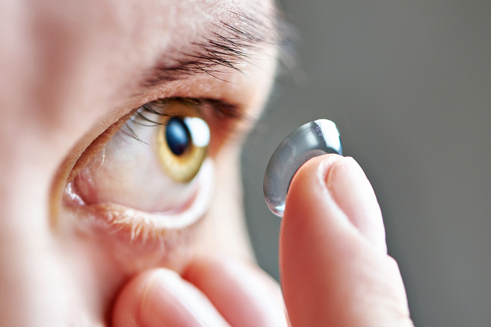 man putting contact lens on eye