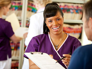 Medical Assistant Smiling And Asking Man To Fill Out Medical Forms - Insurance And Payments Pensacola - Fifty Dollar Eye Guy 5328 N Davis Hwy Pensacola, FL 32503 (850) 434-6387