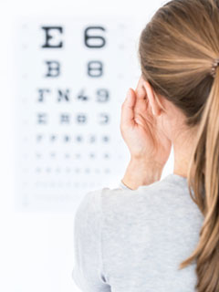 Lady closing one eye and Looking at eye chart -Eye care Services Pensacola FL- Fifty Dollar Eye Guy 5328 N Davis Hwy Pensacola, FL 32503 (850) 434-6387
